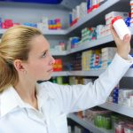 Pharmacist reaching for tablet bottle from shelf